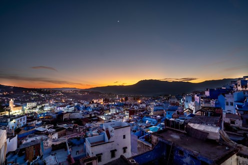 The Moon and Venus visible over the skies of the gorgeous blue city of Chefchauoen, Morocco